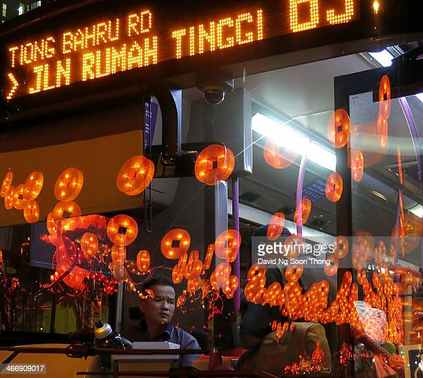 Well framed photo of gold coins and horses reflected on to the front of a bus picking up passengers in Chinatown Singapore. These are deco displayed...