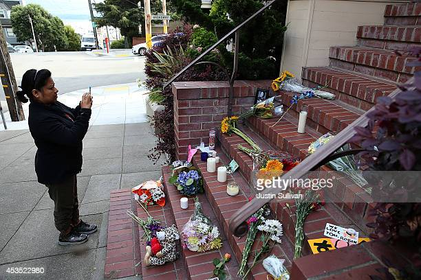 A well wisher takes a picture of a growing memorial in front of the home where actor and comedian Robin Williams filmed the movie Mrs Doubtfire on...