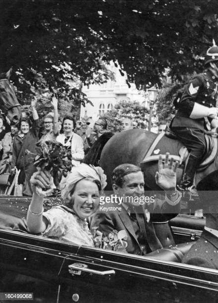 Well wishers greet Princess Beatrix of the Netherlands and her fiancee Claus van Amsberg in an open top car 29th June 1965