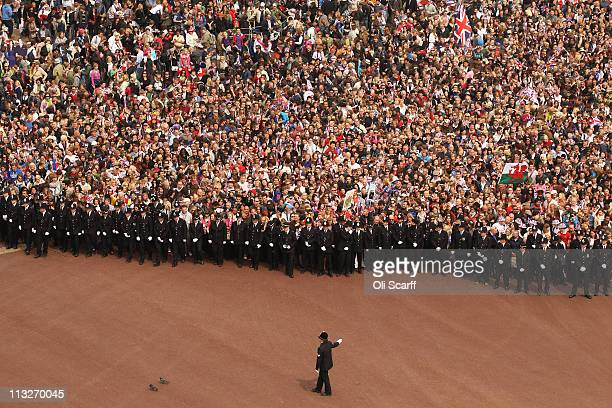 Well wishers surge along the Mall behind the police towards Buckingham Palace to celebrate the Royal Wedding of Prince William Duke of Cambridge and...