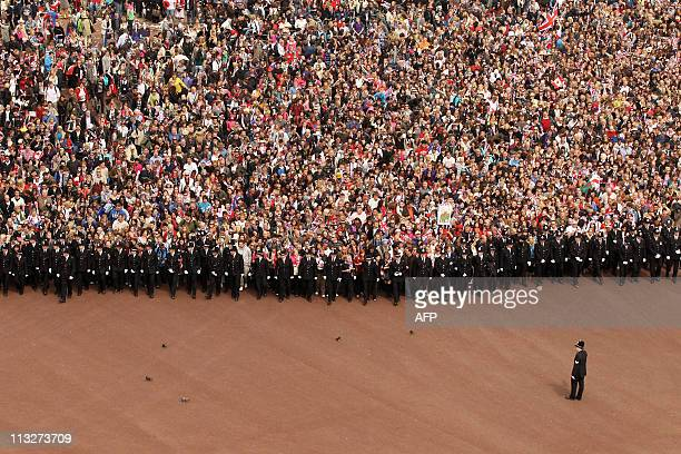 Well wishers surge along the Mall behind the police towards Buckingham Palace to celebrate the Royal Wedding of Prince William, Duke of Cambridge and...