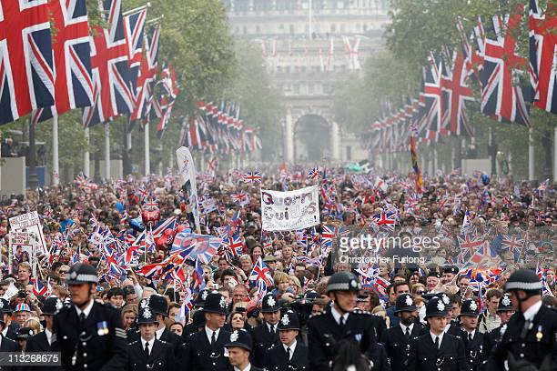 Well wishers with flags and banners surge along the Mall behind the police towards Buckingham Palace to celebrate the Royal Wedding of Prince William...