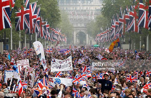Well wishers with flags and banners surge along the Mall towards Buckingham Palace to celebrate the Royal Wedding of Prince William Duke of Cambridge...