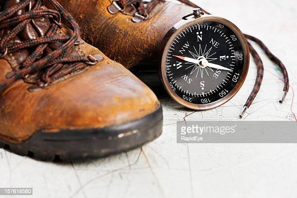 ABGETRAGENES Wanderstiefel mit Karte und Kompass