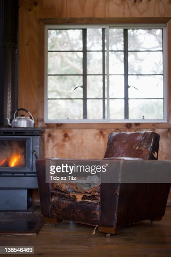 A Well Worn Leather Armchair Next To A Wood Burning Stove ...