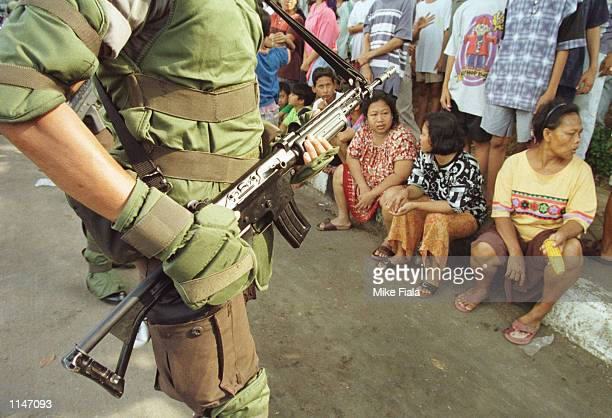A wellarmed riot policeman watches a group of onlookers during an illegal campaign rally by United Development Party supporters in Jakarta Tuesday...