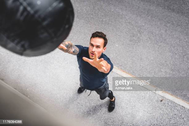 well-conditioned male athlete doing medicine ball wall throw - drive ball sports stock pictures, royalty-free photos & images