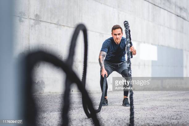 well-conditioned male athlete using battle ropes outdoors - crossfit stock pictures, royalty-free photos & images