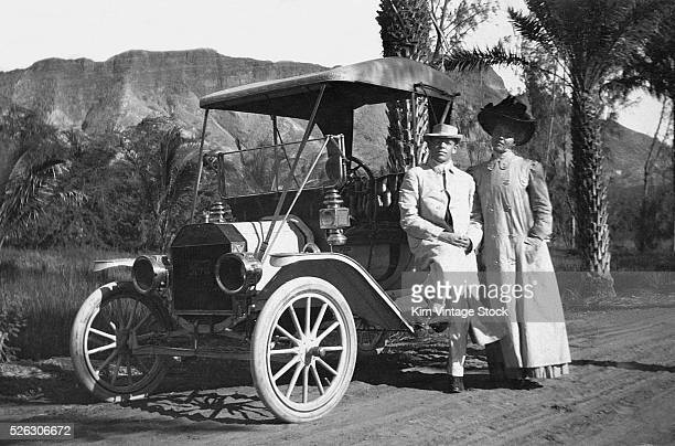 Well-dressed African-American couple stand by their 1909 Ford Touring car in Southern California.
