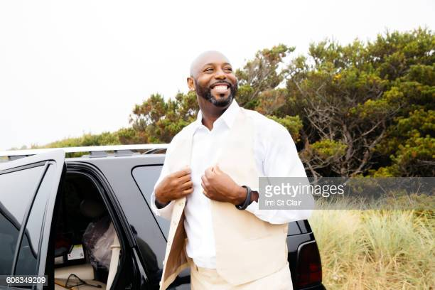 Well-dressed Black man outdoors near car