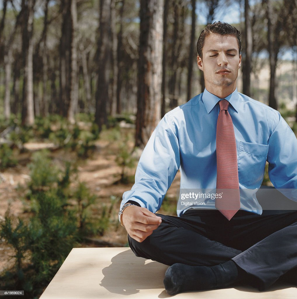 Well-Dressed Businessman Sits in a Forest, Meditating in the Lotus Position : Stock Photo