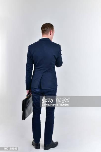 well-dressed businessman standing against white background - rear view stock pictures, royalty-free photos & images