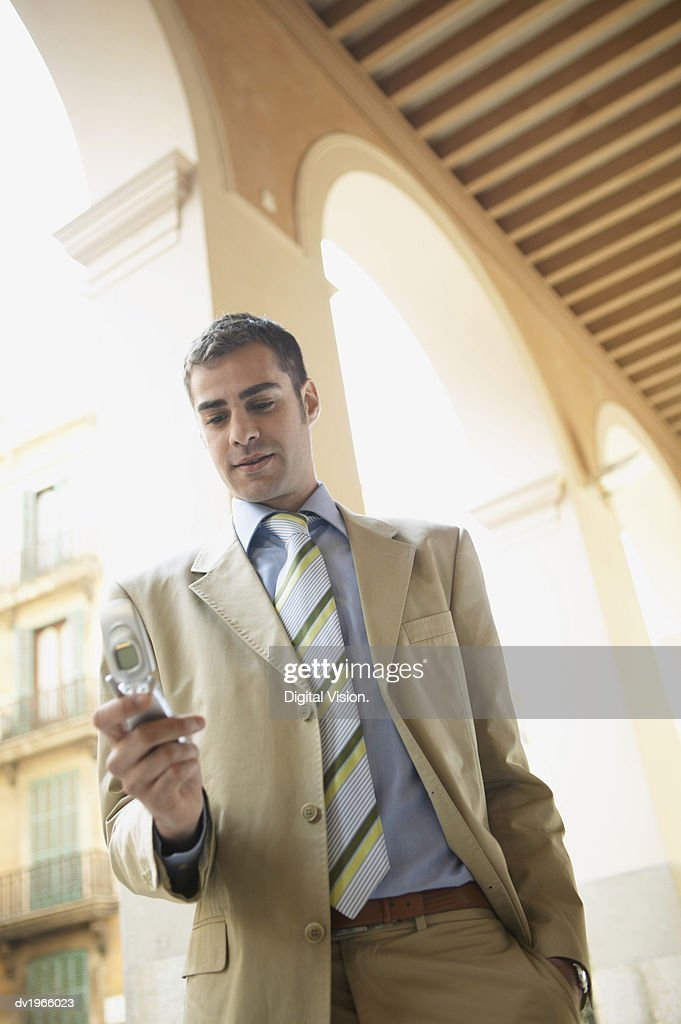 Well-Dressed Businessman Stands Outdoors Texting on His Mobile Phone : Stock Photo