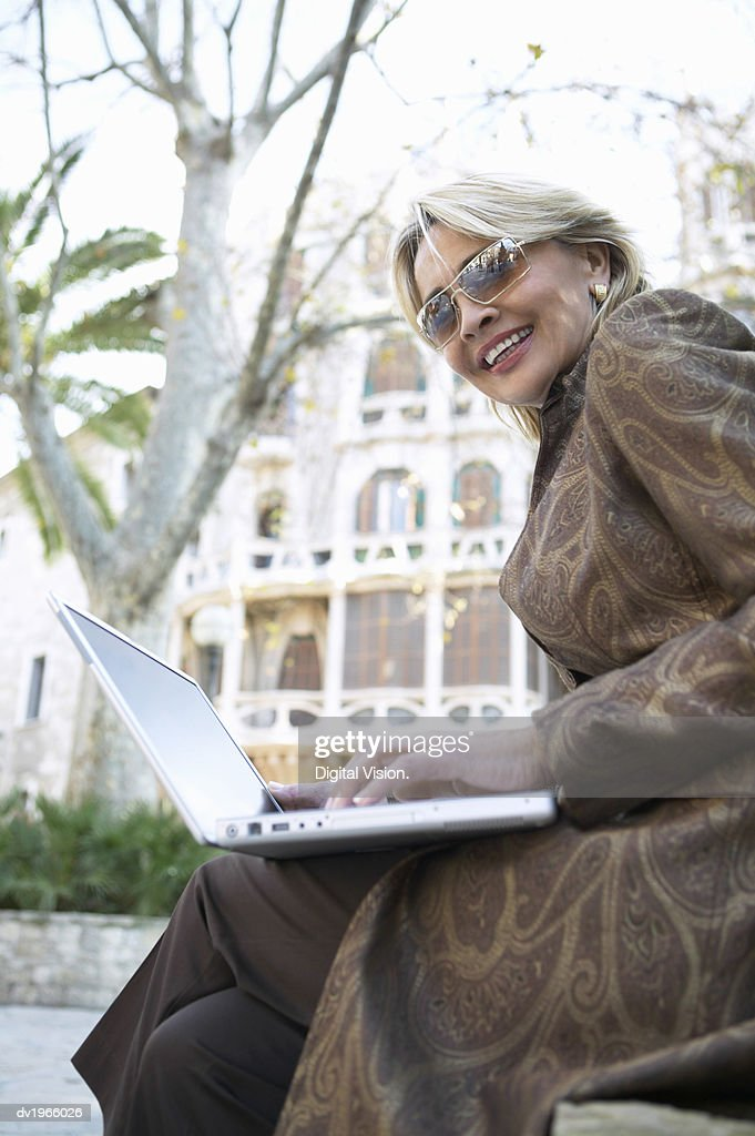 Well-Dressed Businesswoman Sits in an Urban Setting Using Her Laptop : Stock Photo