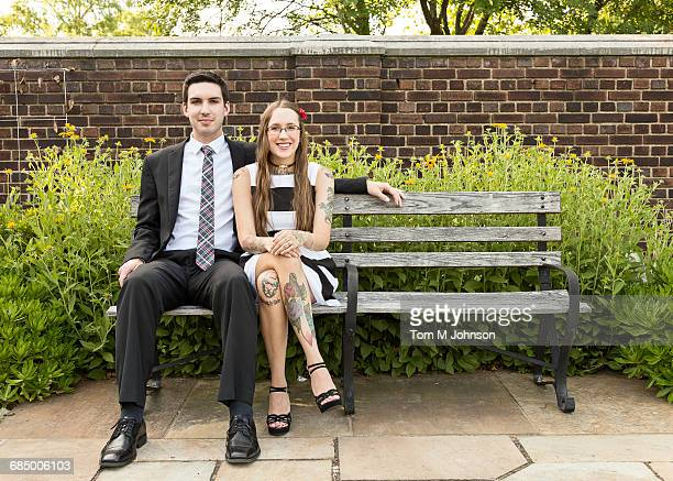 well-dressed caucasian couple sitting on bench at park - mens dress shoes stock pictures, royalty-free photos & images