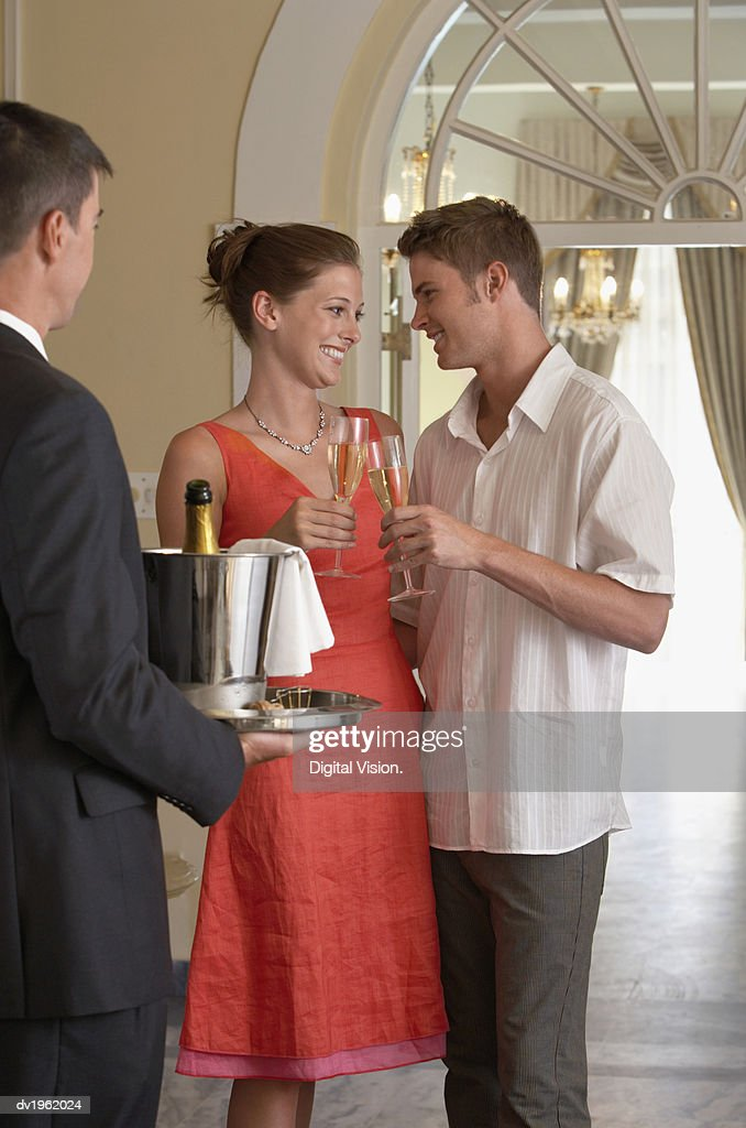 Well-Dressed Couple Make a Toast to Each Other With Champagne, a Waiter Carrying the Champagne Bucket on a Tray : Stock Photo