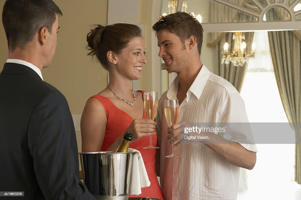 Well-Dressed Couple Make a Toast With Champagne, a Waiter Standing by, Carrying the Champagne Bucket on a Tray : Stock Photo