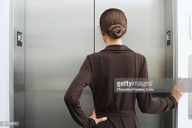 Well-dressed female waiting for elevator, rear view