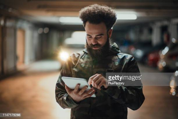 well-dressed hipster influencer posting on his social media accounts - parking valet stock photos and pictures