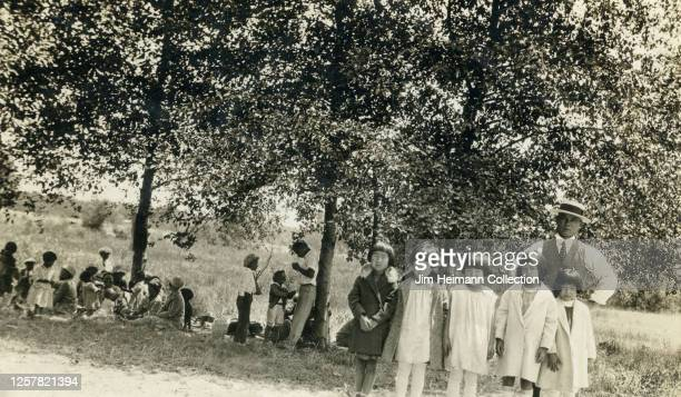 Well-dressed man and group of children take a moment from a picnic to pose for a photo with grass and trees in the background, circa 1925.