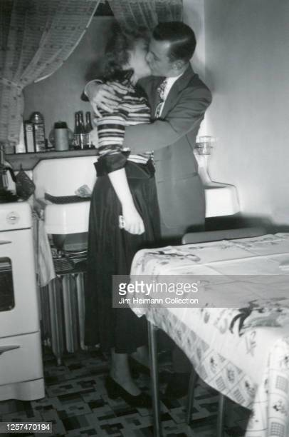 A welldressed man and woman in a kitchen embrace and kiss passionately in front of the sink circa 1941