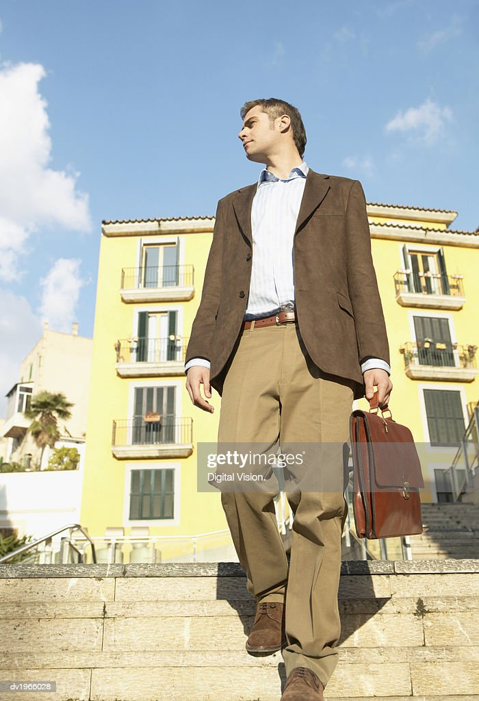 Well-Dressed Man Carrying a Briefcase Descends Steps in an Urban Setting : Stock Photo