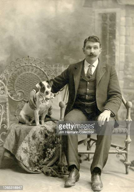 Well-dressed man in a three-piece suit is seated next to small dog on an ornate chair, circa 1906.