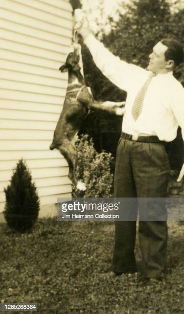 Well-dressed man in slacks and a tie teaches his dog a trick as it leaps into the air, circa 1933.