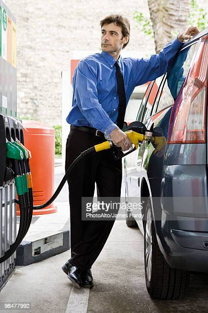 Well-dressed man refueling vehicle at gas station