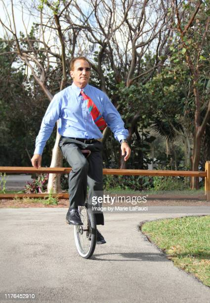 well-dressed man riding a unicycle in the park - fauci stock pictures, royalty-free photos & images