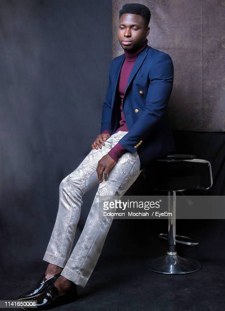 well-dressed man sitting against wall - men fashion stock pictures, royalty-free photos & images