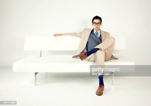 Well-dressed man sitting on a white bench