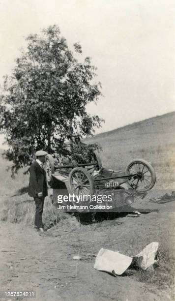 Well-dressed man stands beside a car, which has hit a tree and flipped upside down, circa 1923.