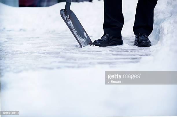 Welldressed 男性、雪をシャベルで取り除く、copyspace