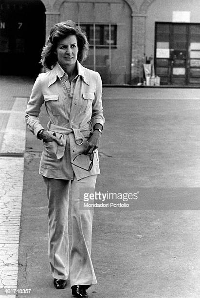 Welldressed Marina Cicogna wearing Englishattitude white pants and jacket walks along the street looking elsewhere in a prudential way representative...