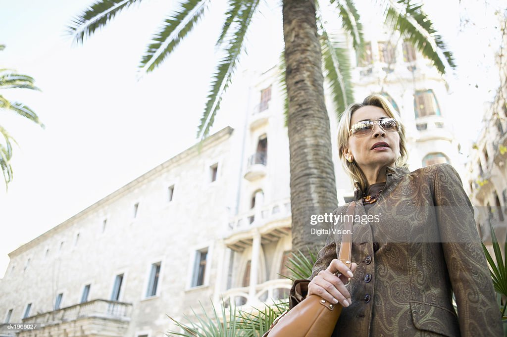 Well-Dressed, Mature Businesswoman Stands by a Palm Tree in an Urban Setting : Stock Photo