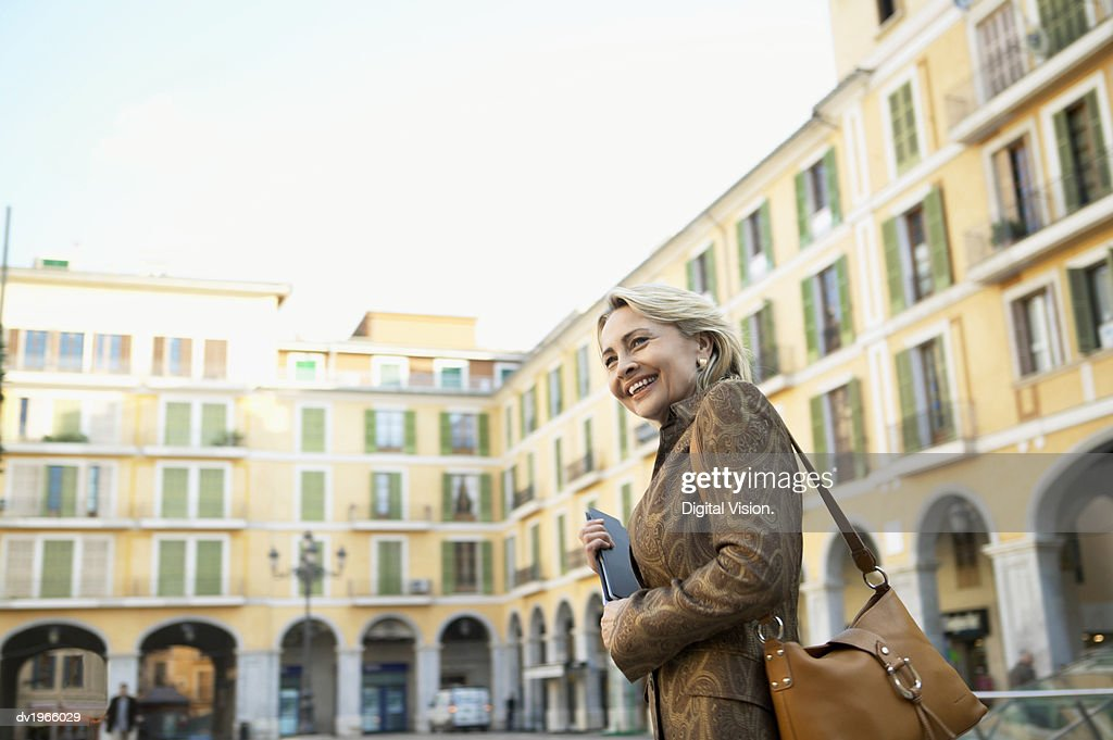 Well-Dressed Mature Woman Walks in a Courtyard : Stock Photo