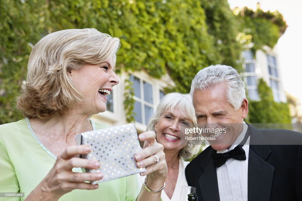 Well-dressed senior couple and woman laughing : Stock Photo
