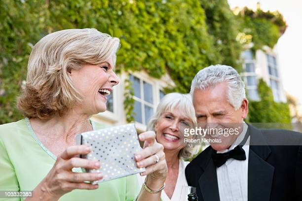 Well-dressed senior couple and woman laughing