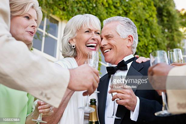 Well-dressed senior couple laughing and drinking champagne