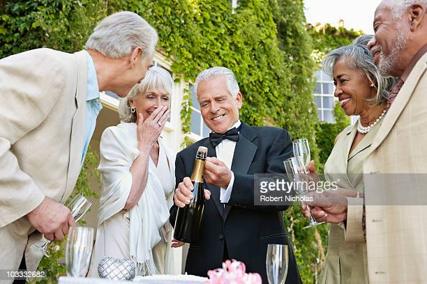 Well-dressed senior couples opening champagne bottle