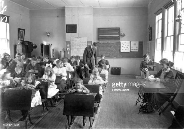 Welldressed students of all ages learn in a oneroom schoolhouse Wisconsin early 1900s Older girls on the right learn sewing and typing