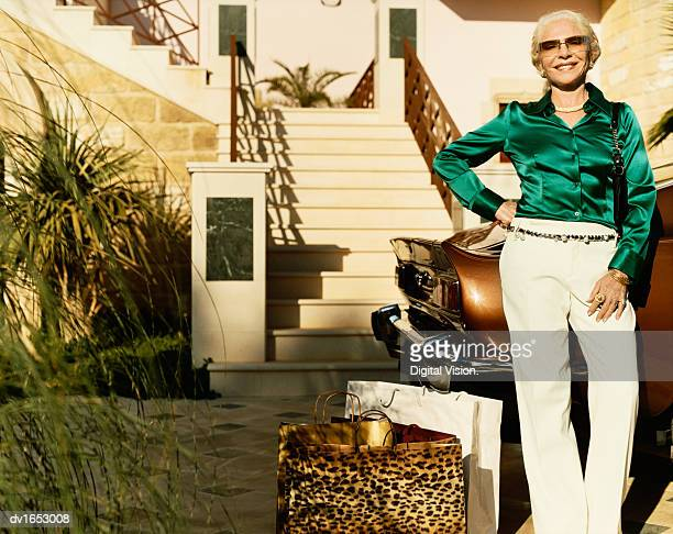 well-dressed wealthy senior woman stands on the driveway by her car with shopping bags - blouse stock pictures, royalty-free photos & images