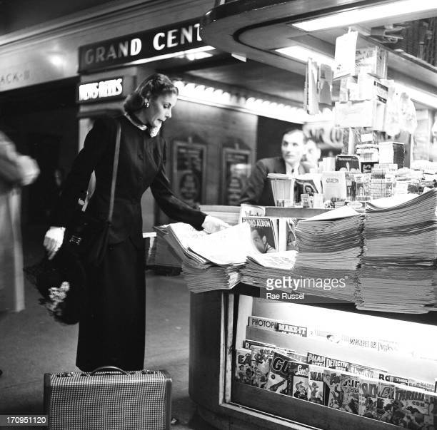 A welldressed woman purchases a newspaper from a newspaper stand inside Grand Central Station New York New York 1948