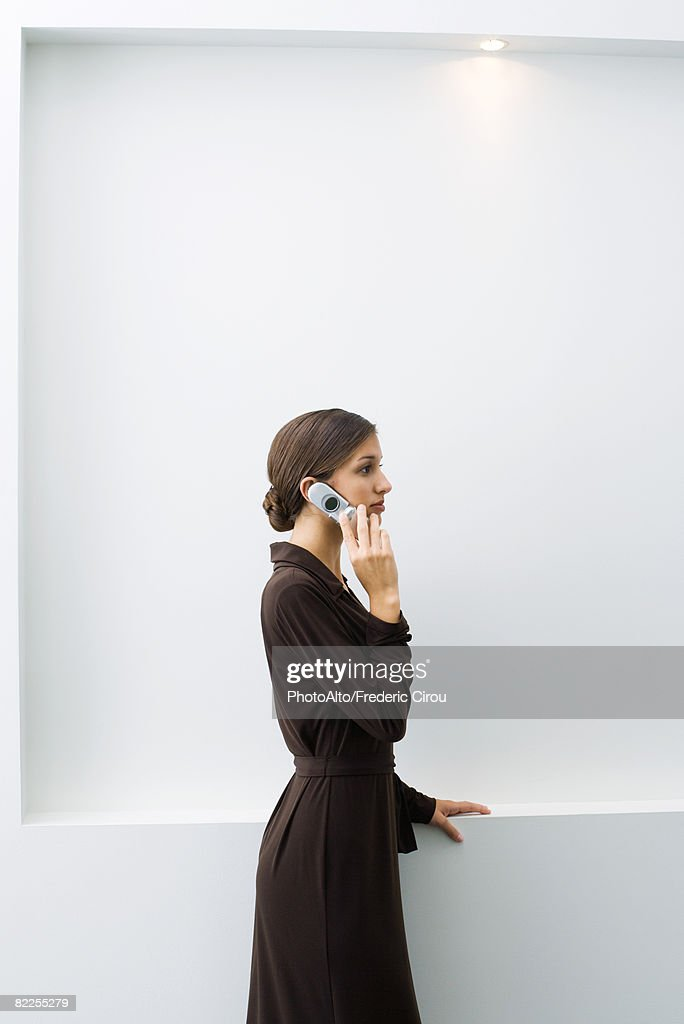 Well-dressed young female using cell phone, standing, side view : Stock Photo