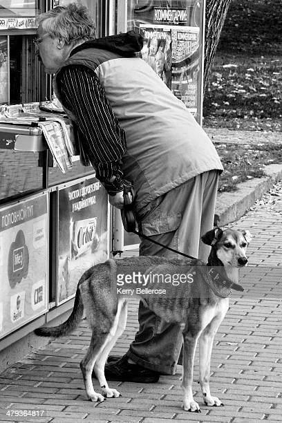 CONTENT] A wellfed middleaged man looks into a newspaper kiosk while holding the leash of a very skinny dog that looks with interest in the opposite...