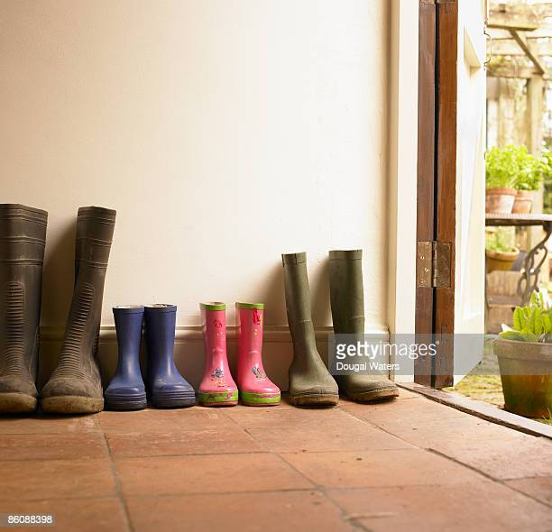 Wellies lined up in hall way.