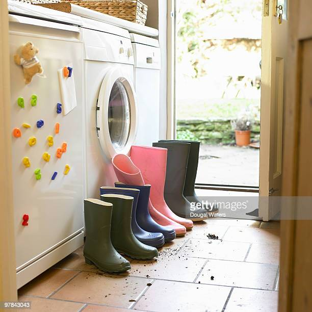 Wellington boots lined up in utility room.