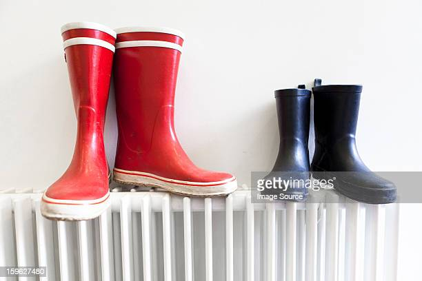 wellington boots on radiator - blue shoe stock pictures, royalty-free photos & images