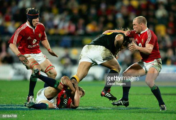 Wellington's Maa Nonu is stopped by Jonny Wilkinson and Neil Back of the Lions during the match between Wellington and the British Lions at The...